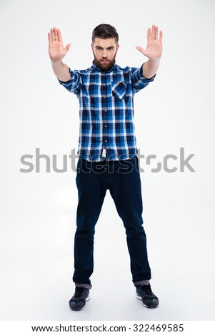 Full length portrait of a casual man showing stop gesture with palms isolated on a white background - stock photo
