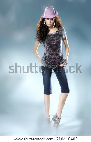 Full length portrait of a casual young fashion in hat posing on light background - stock photo