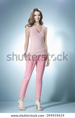 Full length portrait of a casual young fashion model posing in studio - stock photo