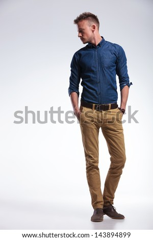 full length portrait of a casual young man standing with both hands in his pockets while looking to his side, away from the camera. on gray background - stock photo
