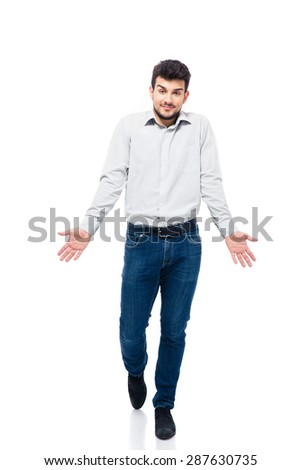 Full length portrait of a casual young man walking and shrugging shoulders isolated on a white background. Looking at camera - stock photo