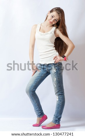 Full length portrait of a caucasian blond woman in blue jeans and pink shoes on gray background - stock photo