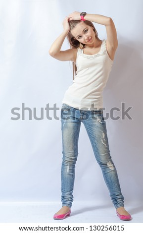 Full length portrait of a caucasian blond woman on gray background - stock photo
