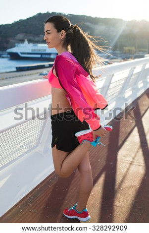 Full length portrait of a charming fit woman stretching legs muscles before start her evening jog in the fresh air, young woman jogger dressed in sportswear workout out during recreation time outside - stock photo
