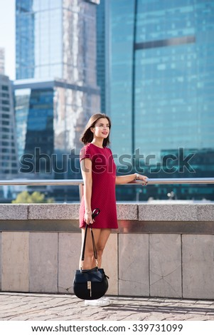 Full length portrait of a charming woman dressed with style waiting for someone while standing outdoors against business center, young gorgeous brunette model with trendy look posing in urban setting  - stock photo