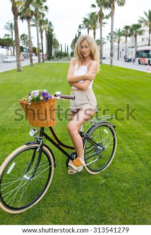 Full length portrait of a charming young woman in stylish clothes sitting on her classic bicycle with a basket of flowers in a cool summer day outdoors,wonderful female cyclist enjoying bike strolling - stock photo