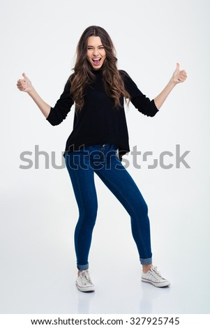Full length portrait of a cheerful casual woman showing thumbs up isolated on a white background - stock photo