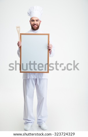 Full length portrait of a cheerful male chef cook iun uniform holding blank board isolated on a white background - stock photo