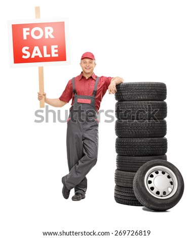 Full length portrait of a cheerful male mechanic standing by a pile of tires and holding a big red for sale sign isolated on white background - stock photo