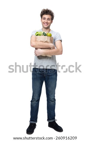 Full length portrait of a cheerful man holding a bag full of groceries - stock photo