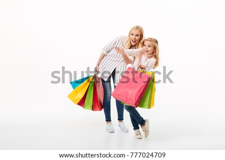 Full length portrait of a cheerful mother and her little daughter standing with shopping bags and pointing away isolated over white background
