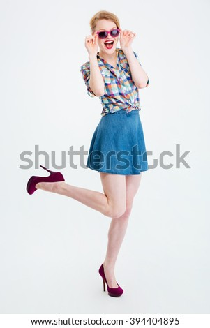 Full length portrait of a cheerful woman in sunglasses posing isolated on a white background - stock photo