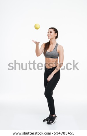 Full length portrait of a cheerful young fitness woman standing and throwing an apple in the air isolated on a white background