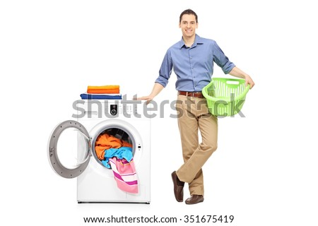 Full length portrait of a cheerful young man holding an empty laundry basket and standing next to a washing machine full of clothes isolated on white background
