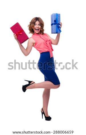 Full length portrait of a cheerful young woman holding gifts isolated on a white background - stock photo