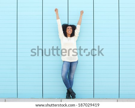 Full length portrait of a cheerful young woman smiling with hands in the air - stock photo
