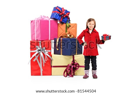 Full length portrait of a child holding a gift and posing next to a pile of gifts isolated on white background