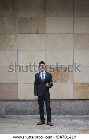 Full length Portrait of a Chinese businessman outside modern office building. Asian businessman smiling & looking at the camera. - stock photo