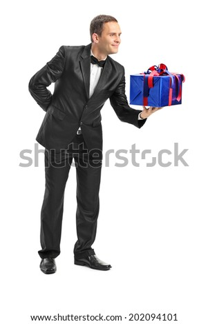 Full length portrait of a classy guy giving a present to someone isolated on white background