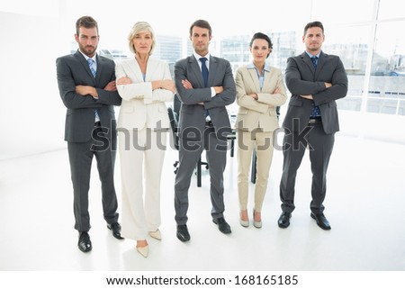 Full length portrait of a confident business team standing with arms crossed in a bright office