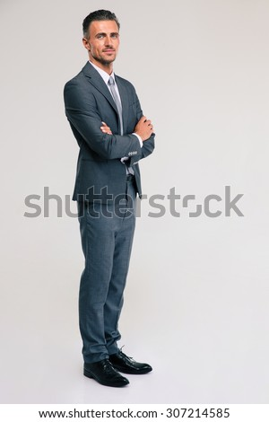 Full length portrait of a confident businessman standing with arms folded isolated on a white background. looking at camera - stock photo