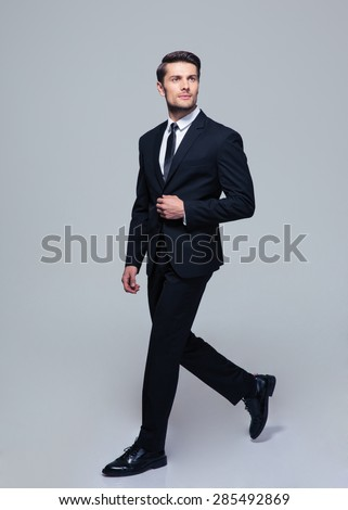 Full length portrait of a confident businessman walking over gray background - stock photo