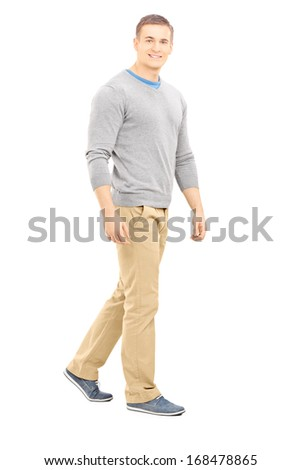 Full length portrait of a confident casual guy walking and looking at camera, isolated on white background - stock photo