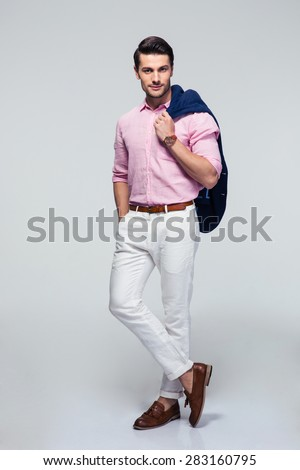 Full length portrait of a confident fashion businessman with jacket on shoulder over gray background. Looking at camera - stock photo