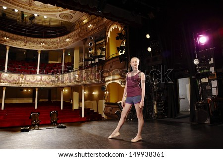 Full length portrait of a confident young ballet dancer on stage - stock photo