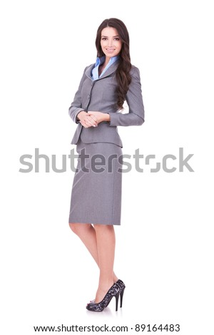 Full length portrait of a confident young business woman standing on white background - stock photo