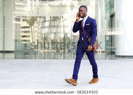 Full length portrait of a confident young businessman walking in the city talking on cell phone  - stock photo