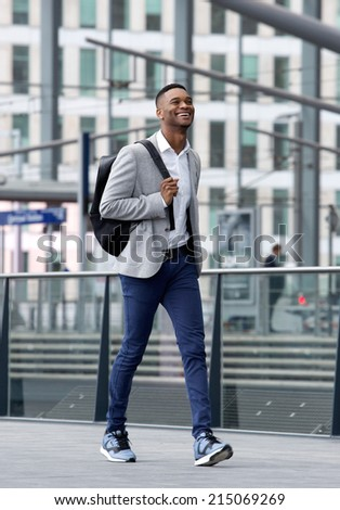 Full length portrait of a cool guy walking at station with bag - stock photo