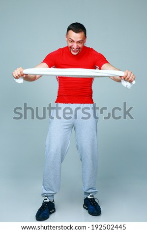 Full length portrait of a crazy sports man with towel on gray background - stock photo