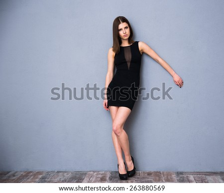 Full length portrait of a cute attractive woman in sexy fashion dress. Posing over gray wall. Looking at camera - stock photo