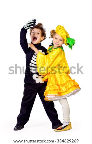 Full length portrait of a cute kids wearing halloween costumes stand with pumpkin. Halloween. Isolated over white. - stock photo