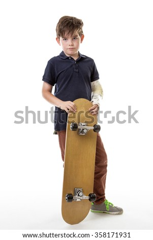 Full length portrait of a cute young boy holding a skateboard with a broken arm  isolated on white background - stock photo