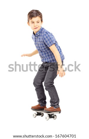 Full length portrait of a cute young boy riding a skateboard isolated against white background - stock photo