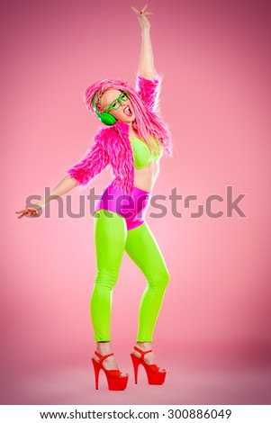 Full length portrait of a dancing glamorous show girl in bright clothes, headphones and with bright pink dreadlocks. Disco, party. Show business. Bright fashion. - stock photo