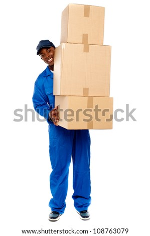 Full length portrait of a delivery boy carrying heavy boxes isolated on white