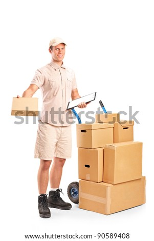 Full length portrait of a delivery boy holding a clipboard posing next to a hand truck with stack of boxes isolated on white background - stock photo