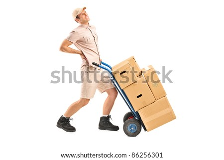 Full length portrait of a delivery boy, suffering from a back pain, pushing a hand truck isolated on white background - stock photo