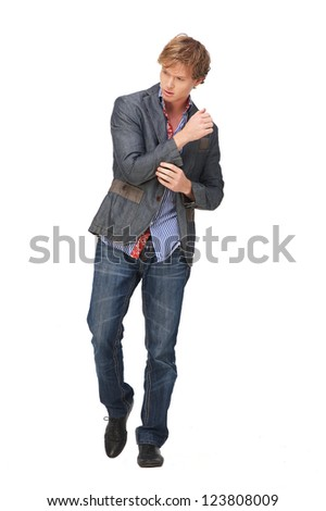 Full length portrait of a European male fashion model wearing jeans and jacket and looking away. Isolated on white background - stock photo