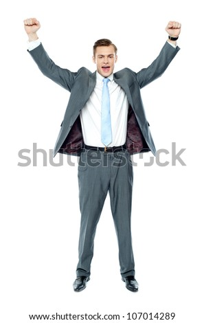 Full length portrait of a excited young executive posing with arms up - stock photo