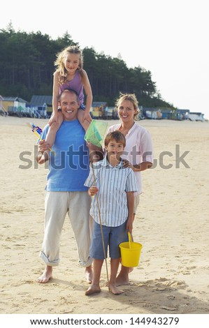 Full length portrait of a family standing on sand at beach - stock photo