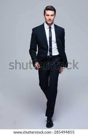 Full length portrait of a fashion male model over gray background. Looking at camera - stock photo