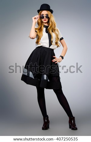 Full length portrait of a fashion model. Beautiful young woman wearing pretty blouse and skirt. Studio portrait over gray background. - stock photo