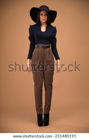 Full length portrait of a fashion woman standing over brown background - stock photo