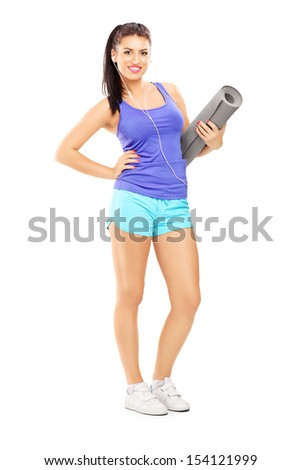 Full length portrait of a female athlete  listening music and holding a mat, isolated against white background - stock photo