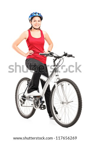 Full length portrait of a female bicyclist posing on a bicycle and giving a thumb up isolated against white background - stock photo