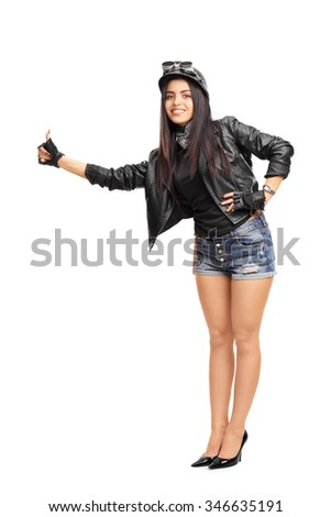 Full length portrait of a female biker in black leather jacket hitchhiking with her thumb isolated on white background - stock photo